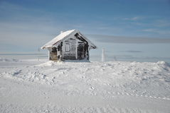 Mountain shelter house. Small mountain shelter house on white snow against blue sky Stock Photos