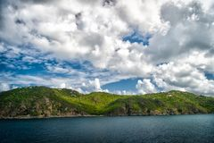 Mountain shore in blue sea on cloudy sky in gustavia, st.barts. Summer vacation on tropical island. Wild nature and environment, e. Cology. Holiday destination Stock Images