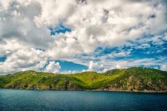 Mountain shore in blue sea on cloudy sky in gustavia, st.barts. Summer vacation on tropical island. Wild nature and. Environment, ecology. Holiday destination stock photos