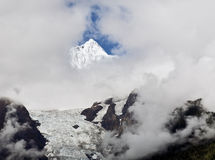 Mountain Shrouded behind Clouds. Mei Li Snow Mountain in northern Yunnan Province behind shrouds of cloud with only its summit visible and the Mei Li glacier Royalty Free Stock Photography