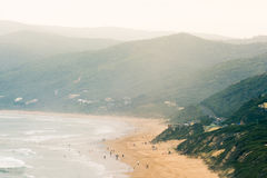 Mountain side beach with glowing summer haze. Picturesque beach along the great ocean road in Australia. raised view of people walking along the beach with a Stock Image