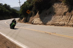 Mountain side motorist on a green motorcycle in Redondo Beach California. Mountain side motorist with green motorcycle and helmet in Malibu California stock image
