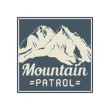 Mountain sign or symbol with text Mountain Patrol Royalty Free Stock Photos