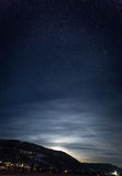 Mountain silhouette against starry nigh sky and shining moon. Beautiful view of mountain silhouette against starry nigh sky and shining moon Stock Photo