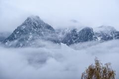 Mountain silhouette fragments through fog and clouds
