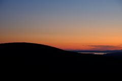 Mountain silhouette and lake at sunset from the top of Cadillac Stock Image