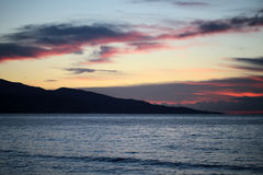 Mountain silhouette in sea after sunset Stock Photos