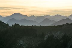Mountain silhouettes with forest and orange sky stock image