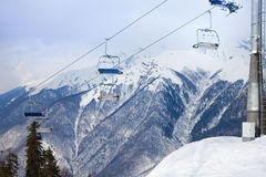 Mountain ski chair lift ropeway and snowy peaks Stock Photos