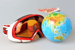 Mountain ski mask, globe and airplane of money on it Stock Photography