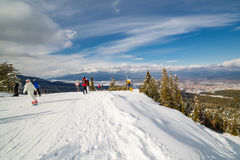 Mountain skiers and snowboarders at top of a slope Royalty Free Stock Image