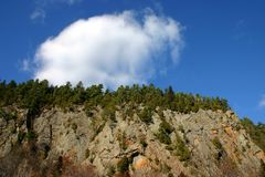 Mountain and sky. Cloud over a blue sky on to of a cliff Stock Images