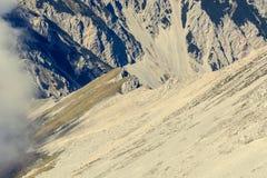Mountain slope finishing with a steep ridge. Stock Image