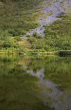 Mountain slope reflected in lake, perfect reflection, rapadalen, Sweden. Walking in Rapdalen valley crossing several beautiful lakes like this one royalty free stock images