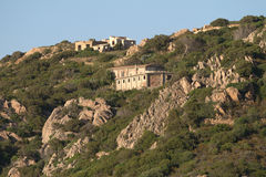 Mountain slope at sunset, ruins. Baja Sardinia Stock Images