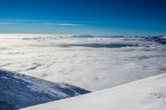 Mountain slopes above the clouds. Mountain slopes covered in snow above the clouds Stock Images