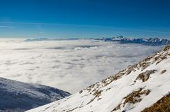 Mountain slopes above the clouds. Mountain slopes covered in snow above the clouds Stock Image