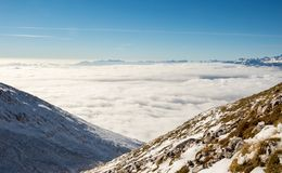 Mountain slopes above the clouds. Mountain slopes covered in snow above clouds Stock Photo