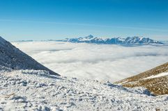 Mountain slopes above the clouds. Mountains slopes covered in snow Stock Photography