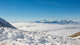 Mountain slopes above the clouds. Mountain slopes covered in snow with mountain chain in the back Stock Photography