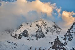 Mountain slopes covered with snow with glaciers in the evening at sunset royalty free stock photo