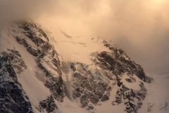 Mountain slopes covered with snow with glaciers in the evening at sunset royalty free stock photography
