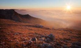 Mountain slopes in the mist at sunrise Stock Image