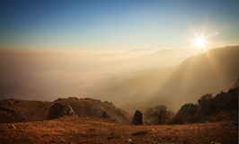 Mountain slopes in the mist at sunset Stock Image