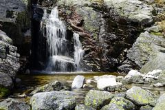 Small waterfall and blurred stream between rocks. royalty free stock photos