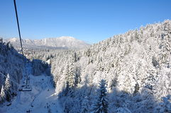 Mountain snow. Snow covered forests of fir trees in mid winter. Behind them there is a mountain ridge with another one far into the horizon. Above it there's a Royalty Free Stock Photo