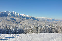 Mountain snow. Snow covered forests of fir trees in mid winter. Behind them there is a mountain ridge with another one far into the horizon. Above it there's a Stock Photography