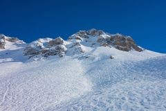 Mountain in the snow and blue sky. Mountains covered with snow. Footprints are seen on the snow. Sunny day. Blue sky Royalty Free Stock Photo