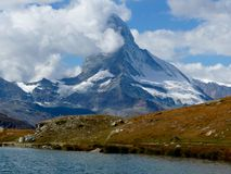Mountain with snow and clouds. Mountain Matterhorn with clouds and lake in the front Royalty Free Stock Image