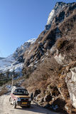 Mountain with snow and leaves less trees. Below with dirt road and four wheel drive tourist car on the way to Zero Point Stock Image