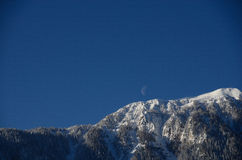Mountain with snow and moon on sky Stock Photos
