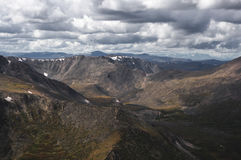 Mountain snow ranges and dramatic valley on the background of cloudy gloom dark sky. Altai mountains Plateau Ukok Siberia Russia stock photography