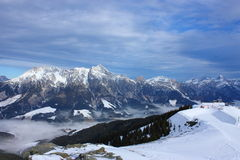 Mountain with snow. Snowy mountains with a foggy valley and a blue but cloudy sky Royalty Free Stock Image