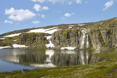 Mountain with snow, waterfall and water Stock Image