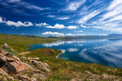 Mountain Songkol lake. Beautiful clouds reflected in water. Kyrgyzstan royalty free stock photo