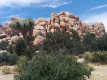Mountain of stacked boulders, greenery, and sky stock images