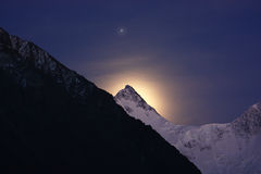 Mountain, star and moon halo. The moon behind mountain also highlights it behind over mountain the bright star (Jupiter) shines royalty free stock photos