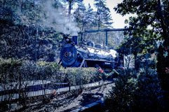 Mountain Steam Engine. A Steam locomotive chugging along through the Trees Stock Images