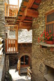 Mountain stone architecture restoration project. Architectural detail of a stone wall, roof and a wood log handrail. Modern mountain architecture restoration Stock Image