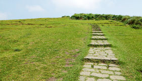 The mountain stone path. The upward stone path on green grass hill to blue sky stock photography