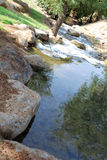 Mountain stream. The small mountain river with waterfalls in the sunny day Royalty Free Stock Images