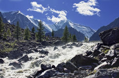 Mountain stream. With breakneck speed rushing into the valley, paving its course between huge boulders Stock Image