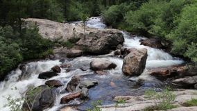 Mountain Stream Cascading and Flowing Around a Large Boulder
