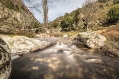 Mountain stream cascading under an ancient Genoese bridge in Cor Stock Photo