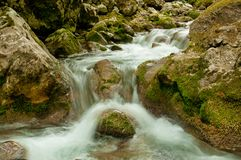 Mountain stream. Mountain fast flowing river stream of water in the rocks with moss Stock Photo