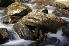 Mountain stream flowing over rocky ground making cascades.  Stock Photos